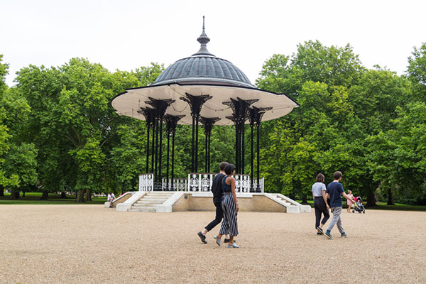 Two groups of people walk through Southwark Park