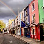 Colourful Notting Hill houses in front of a rainbow