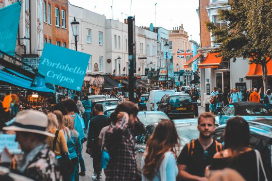 Busy street of Portobello market with shops and people walking along the road