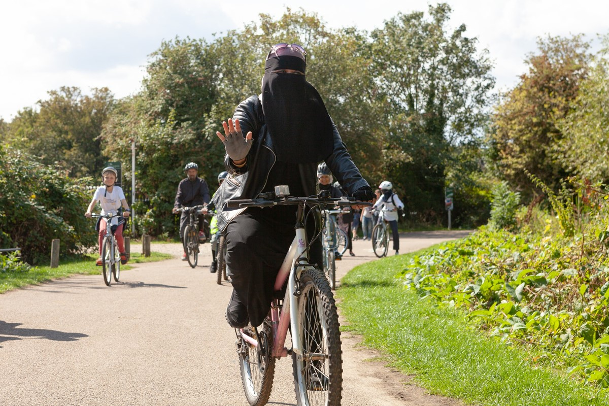 Photo of woman in Islamic dress cycling in the park