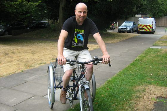 Photo of Neil riding his accessible cycle on a path.