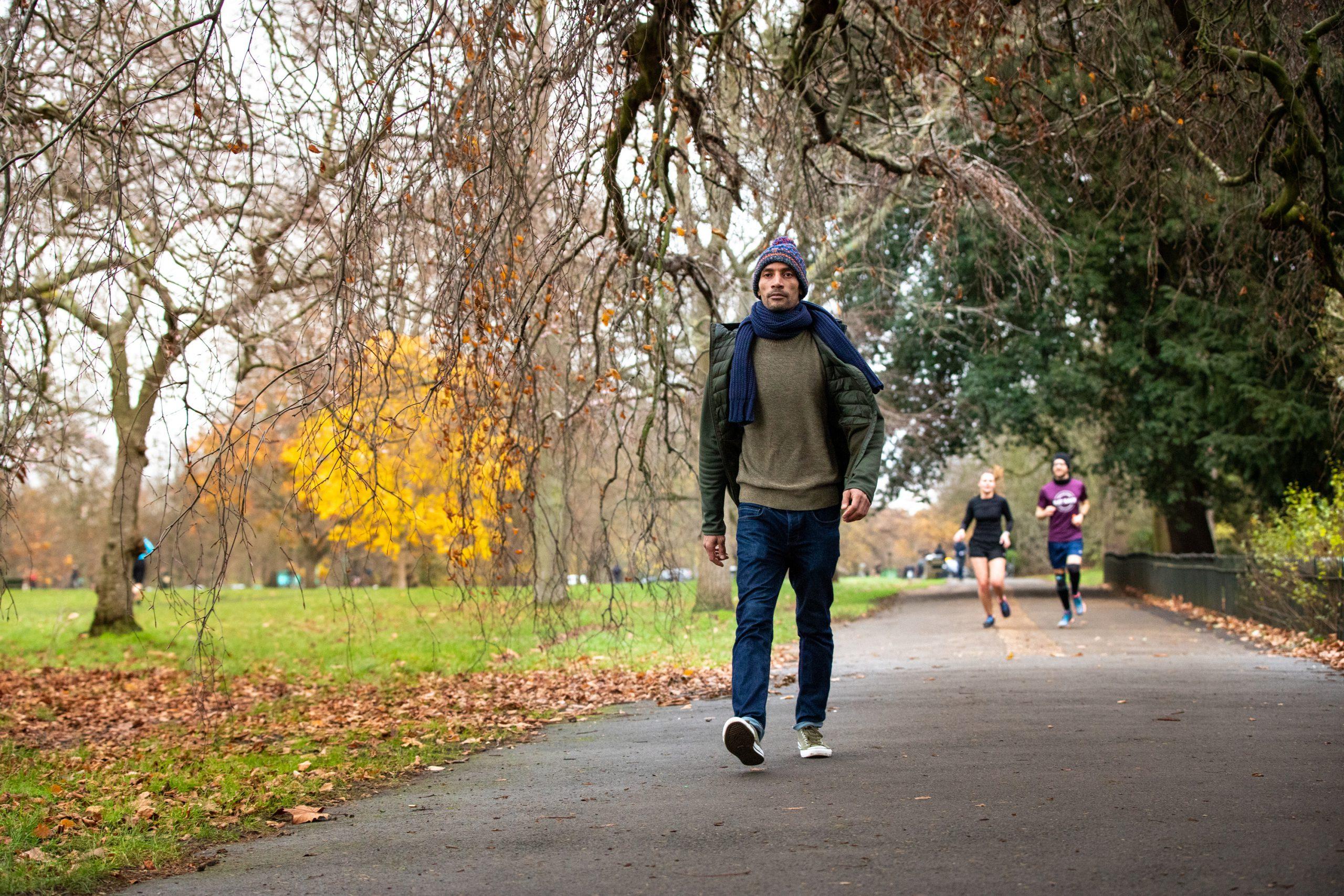A man walks to work through a park in London.