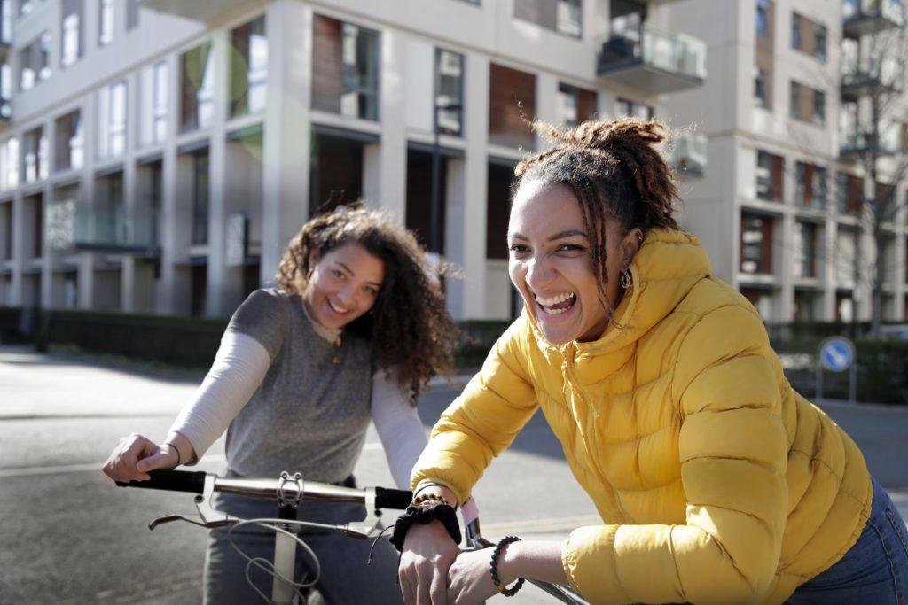 Two girls smiling on their bikes