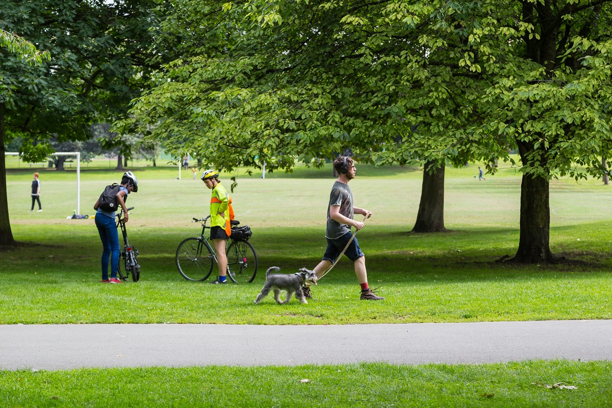 Cyclists and a man walking a dog in Southwark Park