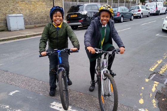 Smiling kids on bikes with helmets waiting at a junction
