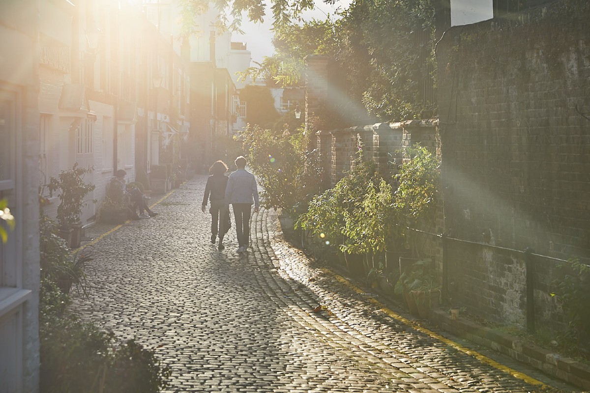 Couple walking down a mews in the sunshine