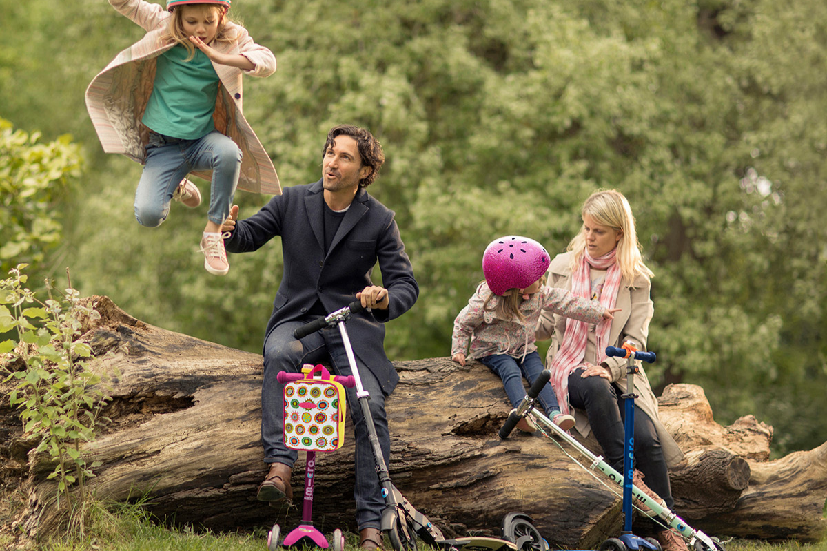 Family sat on tree trunk with scooters