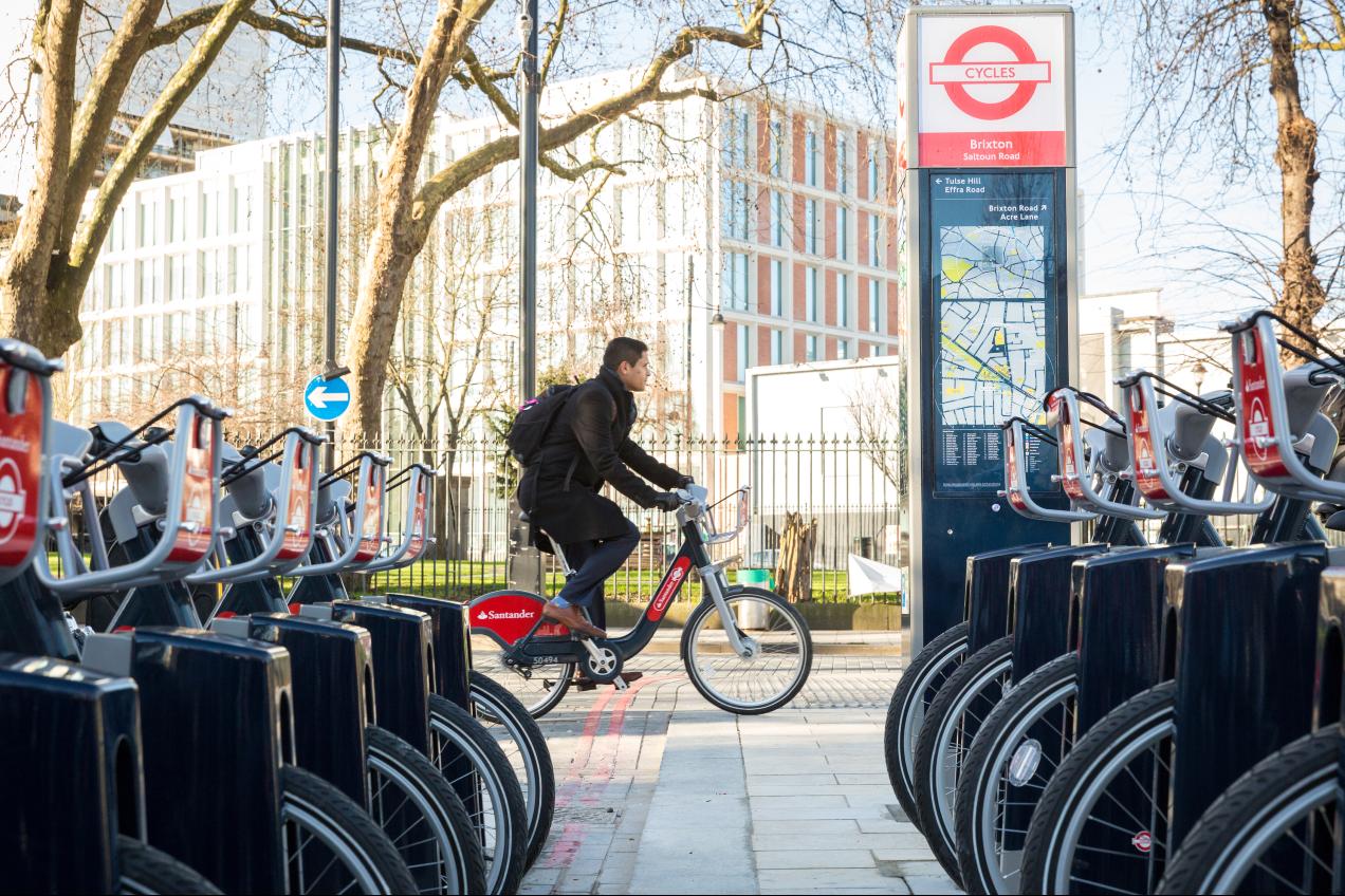 Person cycling past a Santander Cycles docking station