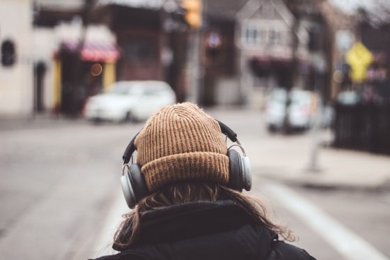 woman walking with hat and headphones