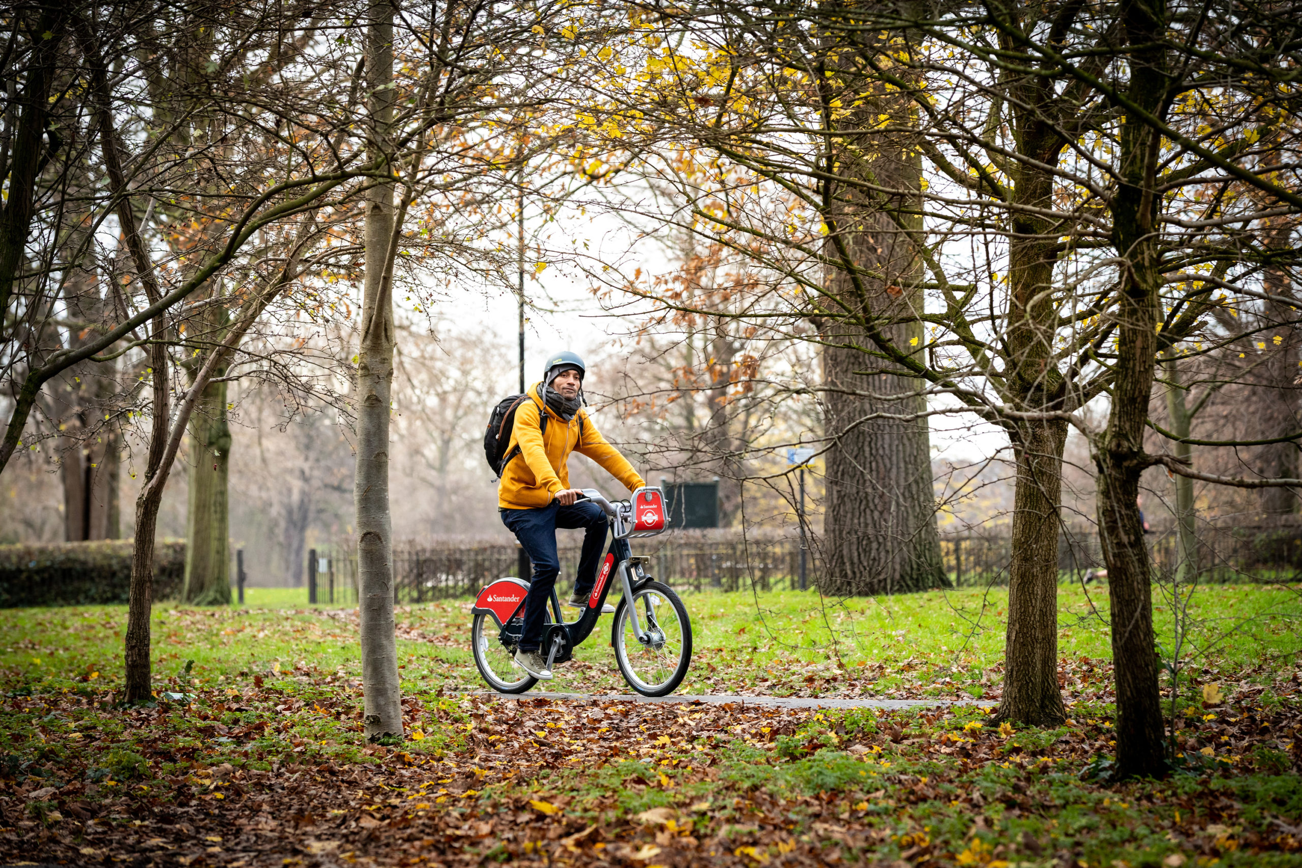 Man cycling in a park during autumn