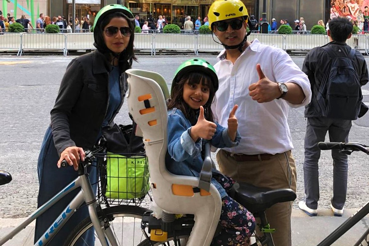 Man giving a thumbs up with his daughter on a family cycle