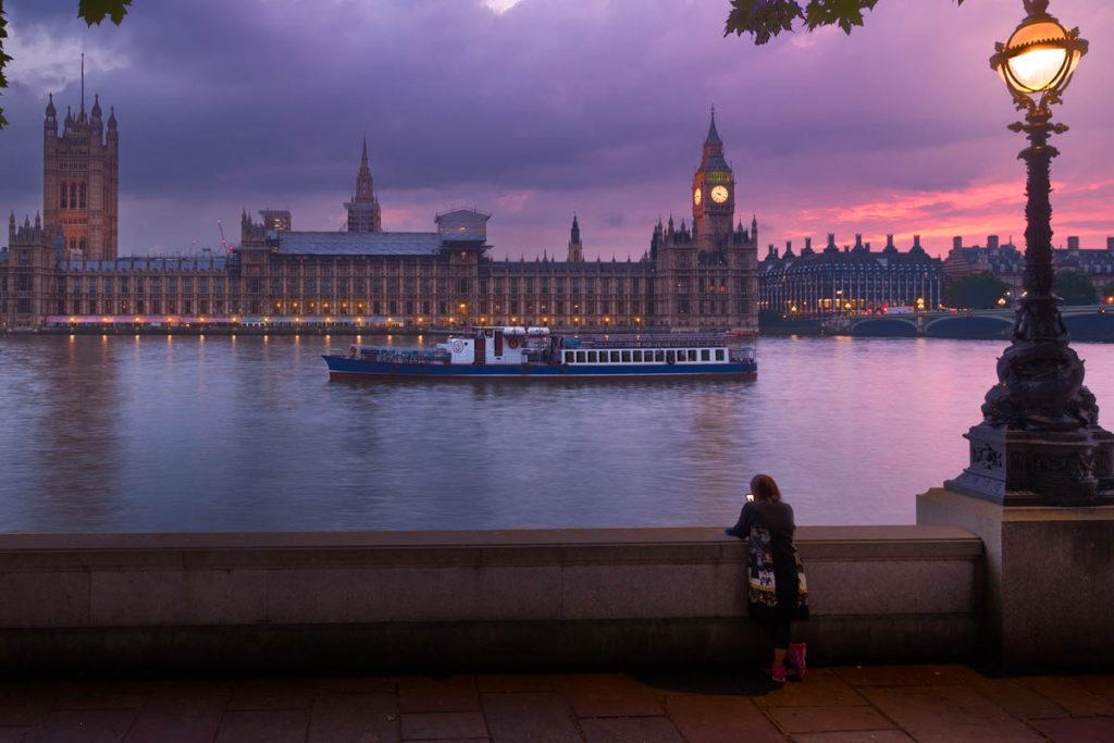 Woman on Southbank looking at Big Ben at sunset.