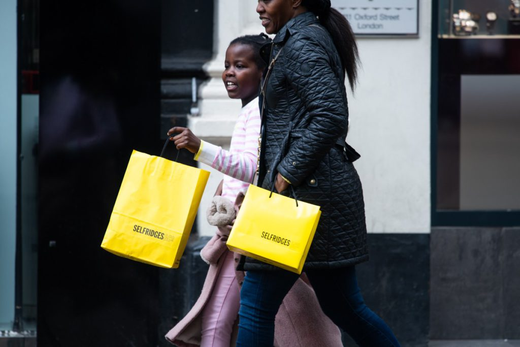 Mother and daughter with Selfridges yellow shopping bags