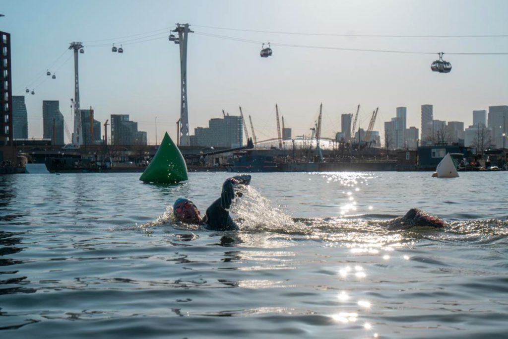 Open water swimming at Royal Docks with Emirates Air Line cable cars in the distance