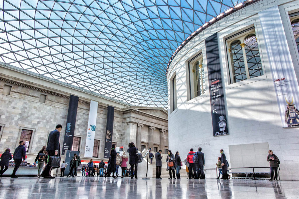 Groups of people inside the main hall of the British Museum.
