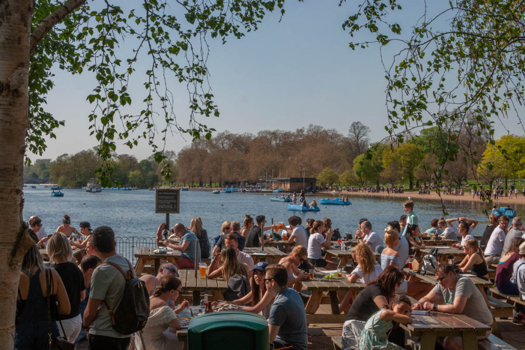 groups of people sat next to the Serpentine at Hyde Park in the sun.