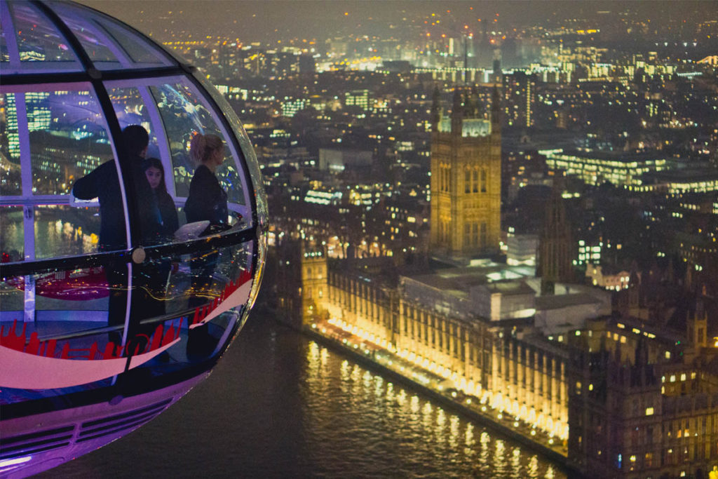 Family inside London Eye car looking over the Houses of Parliament at night.