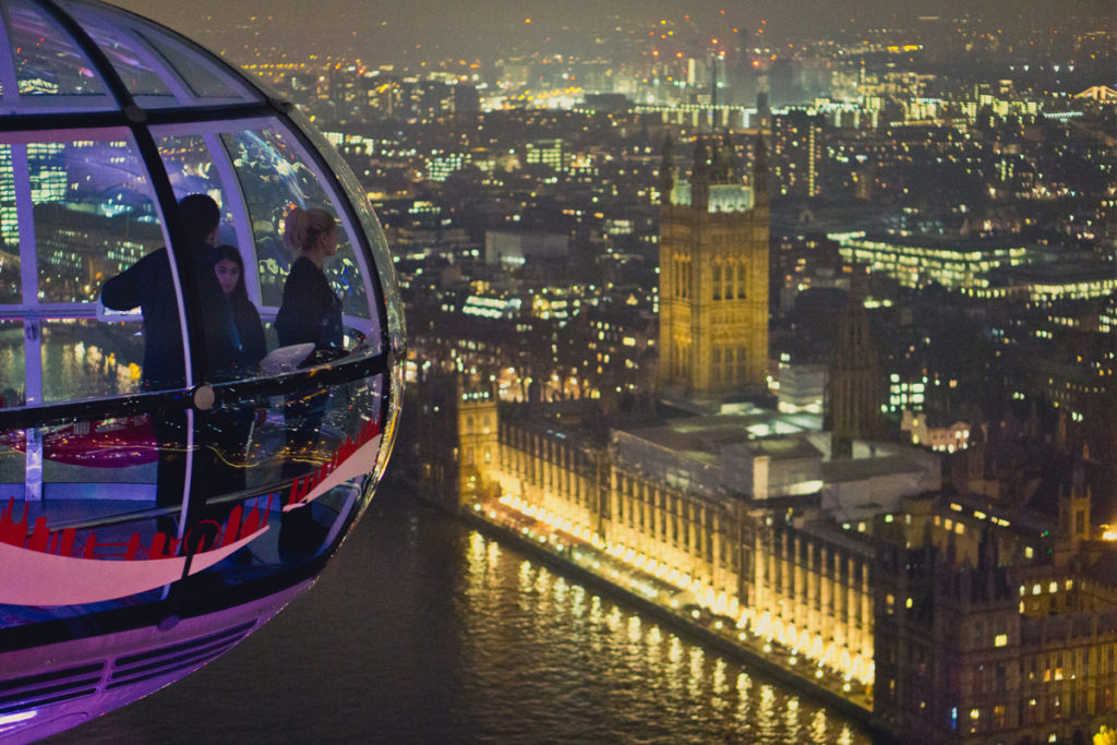 People in the London Eye looking over the Houses of Parliament at night.