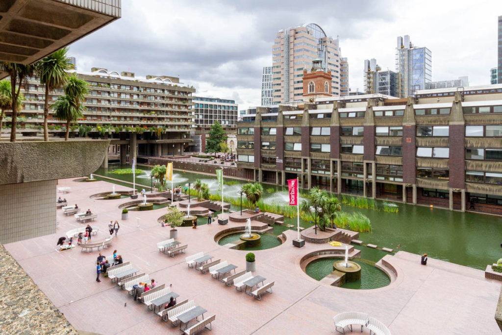 People sat by pond at the Barbican with skyscrapers in the background.