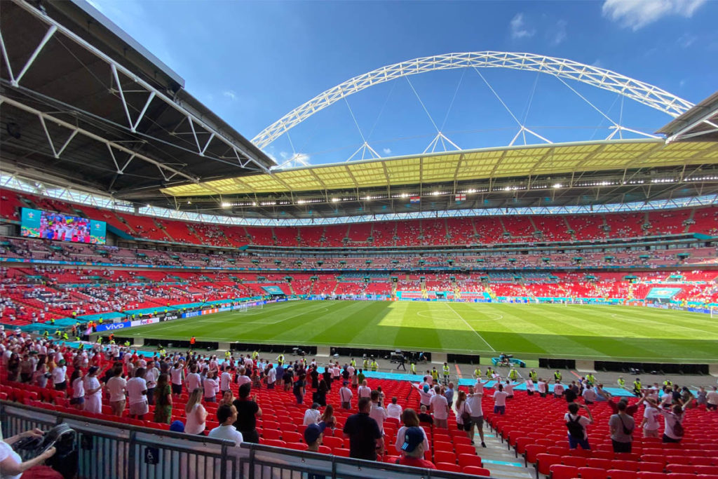 Football fans inside Wembley stadium with famous arch in the background.