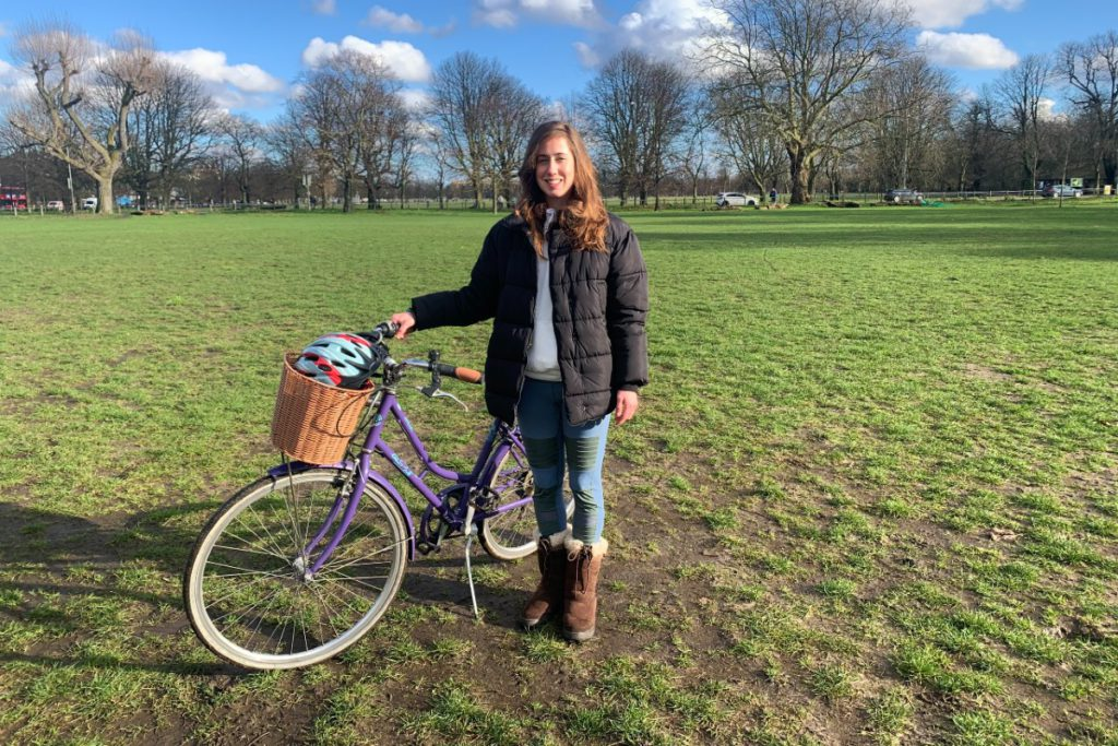 Georgia in a park with her cycle