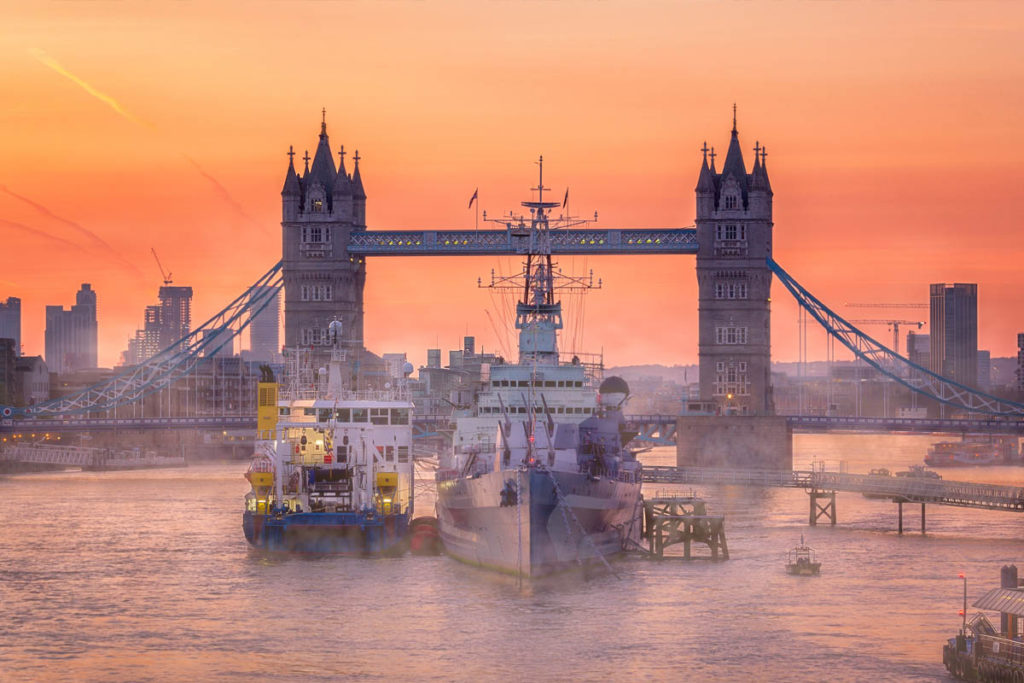 Boats on the Thames in front of Tower Bridge at sunset.