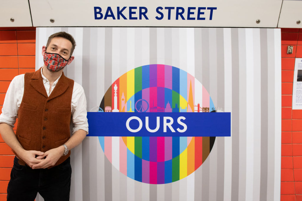 Tim Dunn standing with 'Ours' pride roundel at Baker Street station.