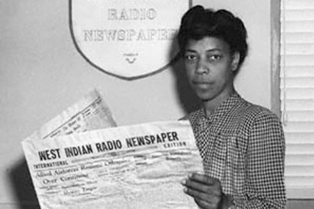 Black and white photo of Una Marson reading West Indian Radio Newspaper.
